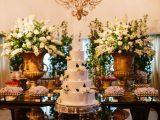 Mesa decorada com bolo de casamento de cinco andares com doces e flores
